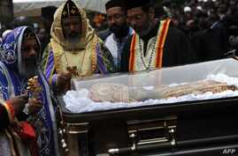 Priests conduct ceremony next to casket bearing remains of Patriarch of the Ethiopian Orthodox Church, Abune Paulos, Aug 23,2012