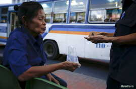 Pranom Chartyothin, a 72-year-old bus conductor, counts coins with a colleague after selling bus tickets in downtown Bangkok, Thailand, Feb. 3, 2016.