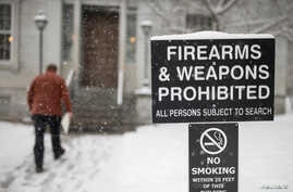 FILE - A man walks past a sign prohibiting firearms and weapons inside the State Legislature in Montpelier, Vermont, March 13, 2018.