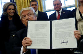 U.S. President Donald Trump holds an executive order dealing with the structure of the National Security Council after signing it in the Oval Office at the White House in Washington, Jan. 28, 2017.