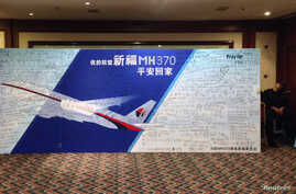 A policeman takes a nap beside a board written with messages for passengers onboard the missing Malaysia Airlines Flight MH370 during a closed meeting held between Malaysian representatives and Chinese relatives of passengers on Flight MH370 at Lido