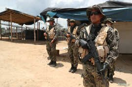 Peruvian military guard an illegal gold mining camp during a operation to destroy illegal machinery and equipment used by wildcat miners in Madre de Dios, Peru, March 5, 2019.