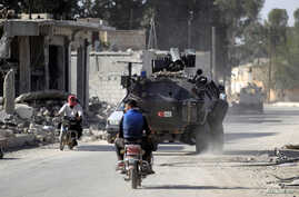 FILE - Men ride motorbikes past a Turkish armored carrier in the northern Syrian rebel-held town of al-Rai, in Aleppo Governorate, Syria, Oct. 5, 2016.