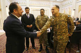 Afghan Foreign Minister, Salahuddin Rabbani  left, shakes hands with a Pakistani officer during a meeting to discuss a road map for ending the war with the Taliban at the Presidential Palace in Kabul, Afghanistan, Tuesday, Feb. 23, 2016.
