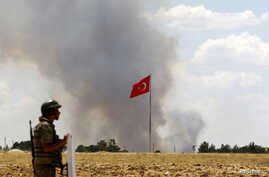 FILE - A Turkish soldier stands guard while smoke rises in the Syrian town of Kobani as it is seen from the Turkish border town of Suruc in Sanliurfa province, Turkey, June 26, 2015.