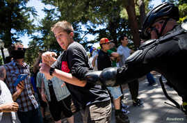 "A police officer grabs a man antagonizing ""anti-fascist"" protestors after multiple people were stabbed during a clash between neo-Nazis holding a permitted rally and counter-protestors on Sunday at the state capitol in Sacramento, California, United"