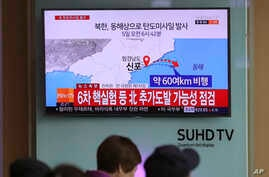 Visitors sit in front of the TV screen showing a news program reporting about North Korea's missile firing, at Seoul Train Station in Seoul, South Korea, April 5, 2017.
