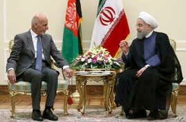 Iranian President Hassan Rouhani, right, talks with his Afghan counterpart Ashraf Ghani at his office in Tehran, Iran,  Aug. 5, 2017.