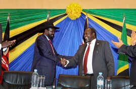 FILE - South Sudan's President Salva Kiir, left, shakes hands with rebel leader and former vice president Riek Machar after signing an agreement to reunify their political party in Arusha, Tanzania, Jan. 21, 2015..