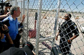 New York City Mayor Bill de Blasio, left, requests entrance to the holding facility for immigrant children in Tornillo, Texas, near the Mexican border, Thursday, June 21, 2018. About 20 mayors from cities across the country are calling for the immedi