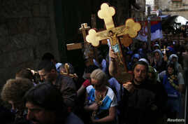 Christian worshippers hold crosses as they take part in a procession along Via Dolorosa on Good Friday during Holy Week in Jerusalem's Old City April 18, 2014. Christian worshippers on Friday retraced the route Jesus took along Via Dolorosa to his cr