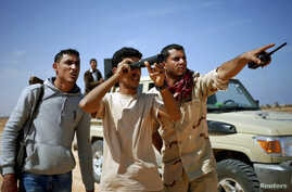 File - Libya Dawn fighters look at Islamic State militant positions near Sirte, Libya, March 2015.