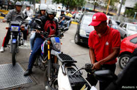 A gas station worker pumps gas into a motorcycle as people wait in line to fill the tanks of their vehicles at a gas station of the state oil company PDVSA in Caracas, Venezuela, March 22, 2017.