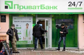 A client enters PrivatBank as others stand by in the center of Kyiv, Ukraine, Dec. 19, 2016.