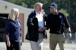 President Donald Trump shakes hands with FEMA Administrator Brock Long as Homeland Security Secretary Kirstjen Nielsen watches after visiting areas in North Carolina and South Carolina impacted by Hurricane Florence, Sept. 19, 2018, at Myrtle Beach I