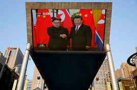 People bicycle past a giant TV screen broadcasting the meeting of North Korean leader Kim Jong Un and Chinese President Xi Jinping, during a welcome ceremony at the Great Hall of the People in Beijing, June 19, 2018.