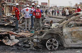 FILE-In this file photo taken on Wednesday, May 21, 2014, Red Cross personnel search for remains at the site of one of Tuesday's car bombs in Jos, Nigeria.  Boko Haram militants are taking over villages in northeastern Nigeria, killing and terrorizin