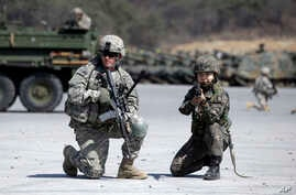 FILE - A U.S. Army soldier and a South Korean Army soldier take their position during joint military exercises between South Korea and the United States in Pocheon, north of Seoul, South Korea, March 25, 2015.