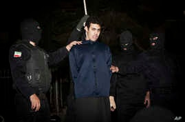 FILE - Iranian policemen prepare to hang a young convict in Tehran, Iran, Jan. 20, 2013. A new U.N. report says Iran has executed 73 minors in the past decade.