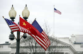 A lamp post is adorned with a Chinese national flag in between two US flags in front of the White House in Washington, DC, January 17, 2011.