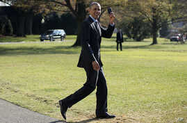FILE - President Barack Obama holds up his Blackberry as he walks on the South Lawn of the White House in Washington.