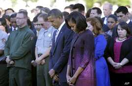 President Barack Obama, first lady Michelle Obama, and members of the White House staff pause during a moment of silence to mark the 11th anniversary of the September 11, 2001 terrorist attacks, on the South Lawn of the White House, in Washington, Se