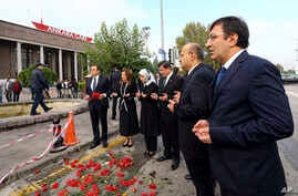 Turkish Prime Minister Ahmet Davutoglu, third right, his wife Sare Davutoglu, third left, his deputies Yalcin Akdogan, second right, and Cevdet Yilmaz, right, pray at the site of an explosion in Ankara, Turkey, Oct. 13, 2015.