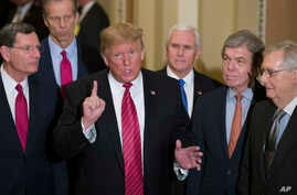 Sen. John Barrasso, R-Wyo., left, and Sen. John Thune, R-S.D., stand with President Donald Trump, Vice President Mike Pence, Sen. Roy Blunt, R-Mo., and Senate Majority Leader Mitch McConnell of Ky., as Trump speaks while departing after a Senate Repu