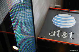 FILE - The signage for an AT&T store is seen in New York, Oct. 29, 2014.