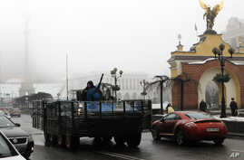 A Ukrainian military vehicle goes down the street on Independence Square in Kiev, Ukraine, Jan. 23, 2015.