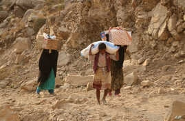 FILE - Yemenis carry relief supplies as they walk along a path outside the city of Taiz, Yemen, Jan. 17, 2016.