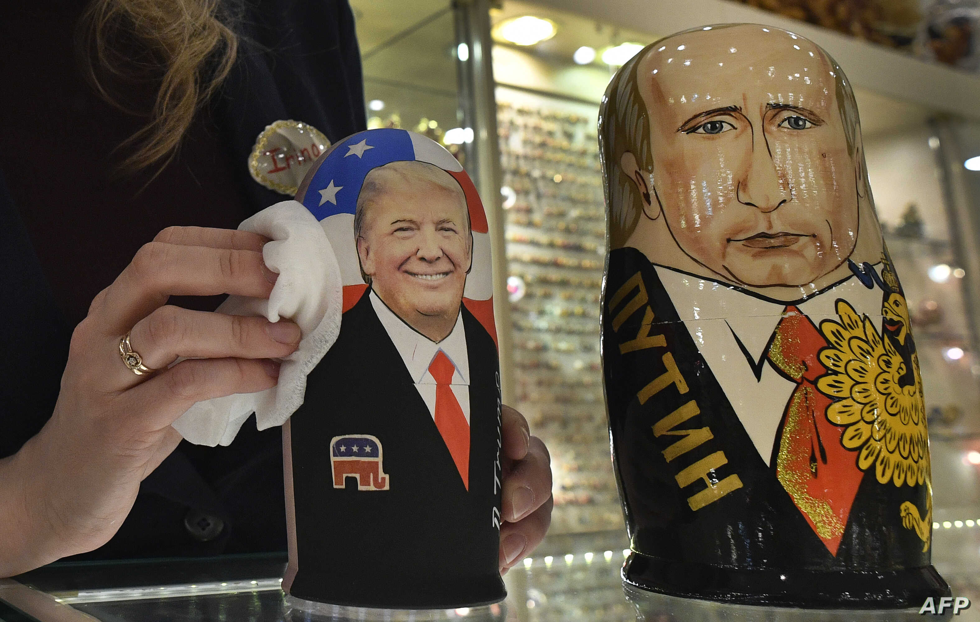 An employee polishes traditional Russian wooden nesting dolls depicting Donald Trump (L), U.S. president-elect at the time, and Russian President Vladimir Putin at a gift shop in central Moscow, Russia, Jan. 16, 2017.