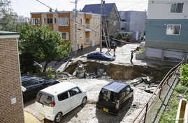 FILE - People look at an area damaged by an earthquake in Sapporo in Japan's northern island of Hokkaido, Japan, in this photo taken by Kyodo Sept. 6, 2018.