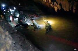 In this handout photo released by Tham Luang Rescue Operation Center, Thai rescue teams walk inside a cave complex where 12 boys and their soccer coach went missing, in Mae Sai, Chiang Rai province, in northern Thailand, July 2, 2018.