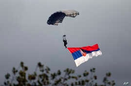 """A Serbian army paratrooper descends during a military parade in Belgrade, Serbia, Thursday, Oct. 16, 2014. Waving Russian and Serbian flags and displaying banners """"Thank You Russia,"""" tens of thousands came to see the parade in Belgrade attended by Vl"""