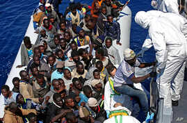 Migrants crowded in an inflatable dinghy await rescue by the Italian coast guard's vessel Denaro off the Libyan coast, in the Mediterranean Sea, Wednesday, April 22, 2015. European Union leaders have promised more aid to help stem the tide of migrant