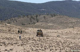 FILE - Tunisian soldiers patrol near the border with Algeria as seen from the area of Mount Chambi.