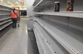 A woman walks between the empty shelves of a supermarket in Caracas, Jan. 11, 2018.