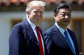 President Donald Trump and Chinese President Xi Jinping walk together after their meetings at Mar-a-Lago, April 7, 2017, in Palm Beach, Fla.