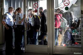 Migrants arrive at Rodby in Denmark, as Danish police guide them into a building at the harbor, Sept. 8, 2015.