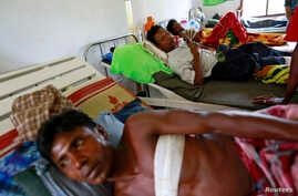 Burmese Rohingya men who were shot by police during a riot on Friday rest in Dapaing district clinic, outside of Sittwe, August 11, 2013.