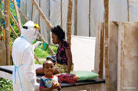 FILE - A health worker, wearing head-to-toe protective gear, offers water to a woman with Ebola at a treatment center for infected people, as a young boy stands nearby in Kenema Government Hospital, in Kenema, Eastern Province, Sierra Leone.