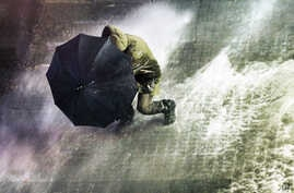 A man uses an umbrella as Turkish riot police fire water cannons and tear gas at hundreds of demonstrators who try to march to the city's main Taksim Square in Istanbul, Feb. 8, 2014 in protest of legislation which critics say will tighten government