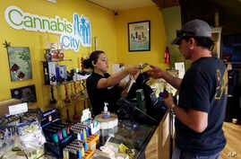 FILE - Jessica Mann, left, gives change to a customer following a recreational marijuana purchase at Cannabis City, in Seattle, July 7, 2016. Officials in states like Oregon where marijuana is legal are trying to curtail smuggling of pot to other sta