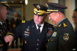 U.S. - China: U.S. Army Chief of Staff Gen. Mark Milley, left, introduces members of his staff to China's People's Liberation Army (PLA) Gen. Li Zuocheng, right, during a welcome ceremony at the Bayi Building in Beijing, Tuesday, Aug. 16, 2016.