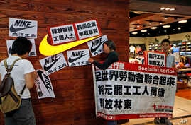 Protesters hold banners and placards during a protest outside a Nike shop at a shopping mall during Labor Day in Hong Kong, May 1, 2014 to support workers on strike at Yue Yuen Industrial Holdings Ltd. in China.
