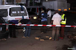 Bomb experts carry out investigations at the scene of an explosion along Biashara street in the Kenyan Coastal city of Mombasa, May 22, 2014.