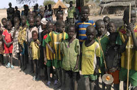 FILE - Children look at WFP food trucks arriving on February 13, 2016 in Pierri village of Jonglei State for the first time in three years since fighting broke out in December 2013 forcing locals here to survive on wild plants, trees and leaves.