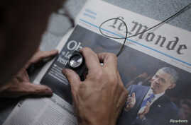 FILE - An employee checks a copy of the freshly-printed French daily evening newspaper Le Monde.