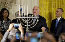 Israeli President Reuven Rivlin lights a menorah and sings, joined by President Barack Obama, first lady Michelle Obama and Nechama Rivlin, during a Hanukkah reception in the East Room of the White House in Washington, Dec. 9, 2015.